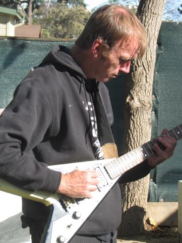 James Pollard playing his electric guitar, photo by Bea Garth