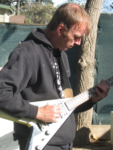 James Pollard playing his electric guitar, photo by Bea Garth